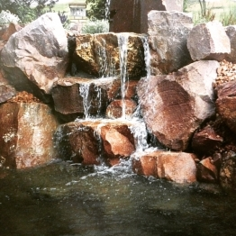"Water cascades down huge rocks. See ""Too Late for Regrets"" page 251 for a description of Timothy's water feature."